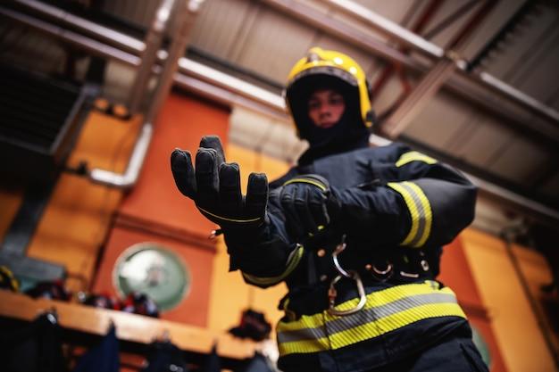 Close-up do bombeiro calçando luvas e se preparando para a ação em pé no corpo de bombeiros.