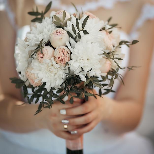 Close-up do buquê da noiva, menina tem grandes flores nas mãos