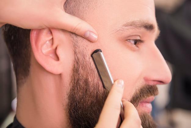 Close-up do cabeleireiro que barbeia uma lâmina antiquado.