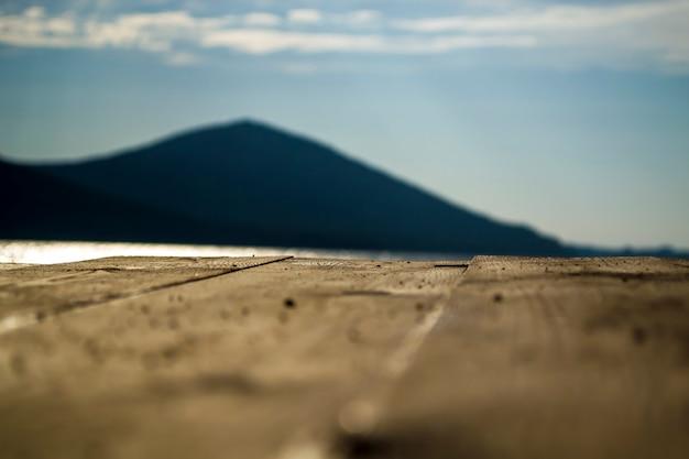 Close up do cais da placa em uma montanha ao fundo com um cais no grande lago lakea no monte