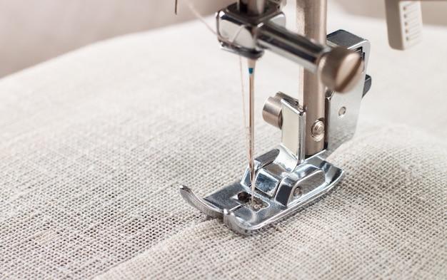 Close-up do calcador de máquina de costura moderna e a peça de roupa de costura da agulha.