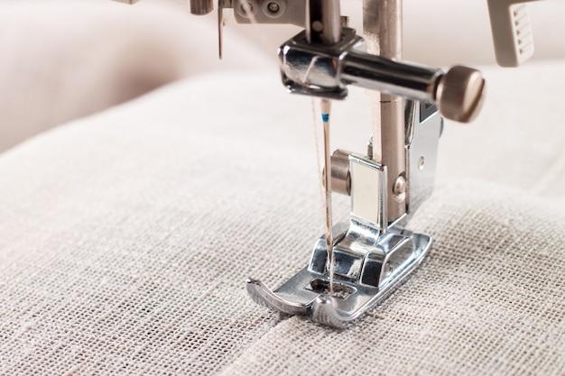 Close-up do calcador de máquina de costura moderna e item de roupas de costura de agulha.