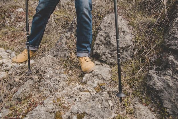 Close-up do caminhante com botas e bengalas