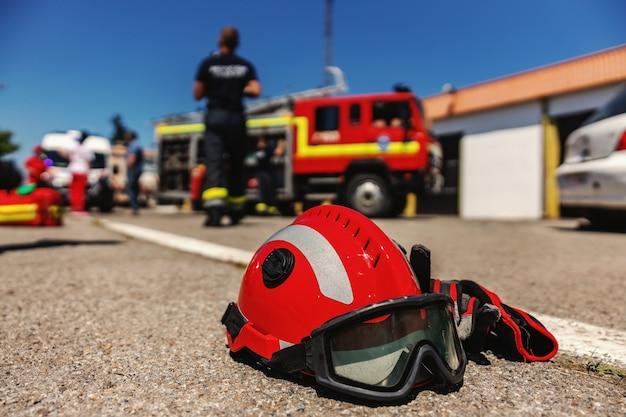 Close up do capacete protetor. no fundo estão bombeiros e caminhão de bombeiros.