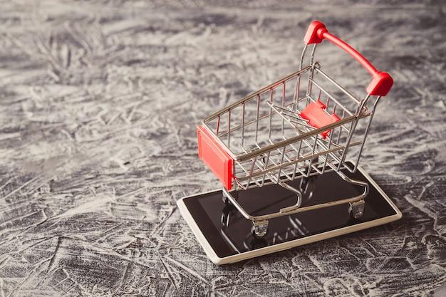 Close up do carrinho de compras no smartphone na mesa de concreto.
