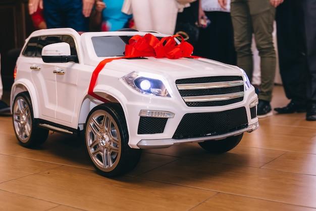 Close up do carro elétrico do bebê com fita vermelha. festa de aniversário. gu