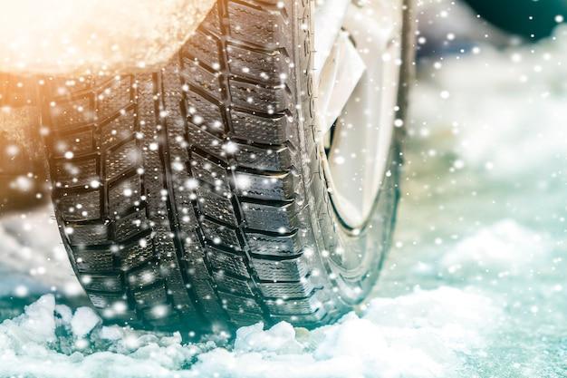 Close-up do carro roda no pneu de inverno na estrada nevada