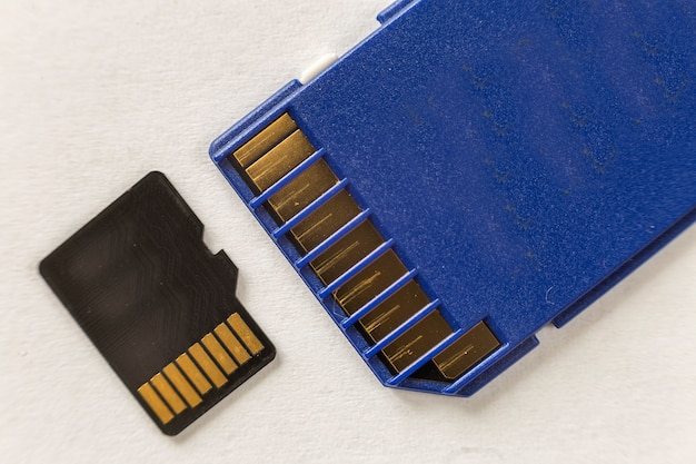 Close-up do cartão de memória micro sd e adaptador sd isolado no espaço branco da cópia. conceito de tecnologia moderna.