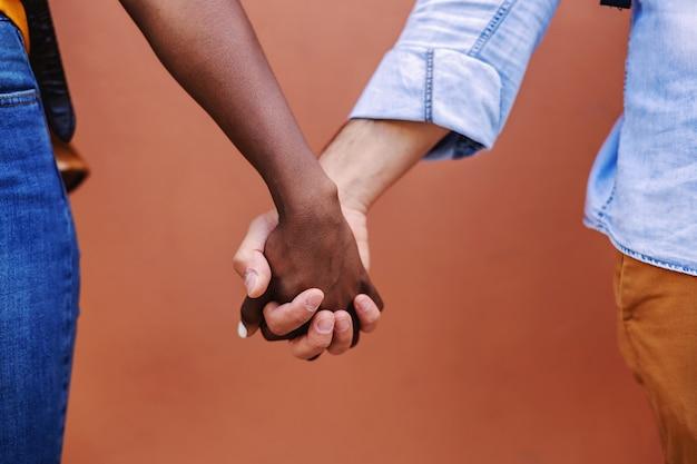 Close-up do casal multicultural de mãos dadas.