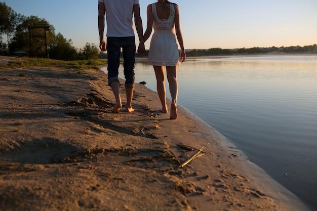 Close-up do casal segurando as mãos com fundo de praia