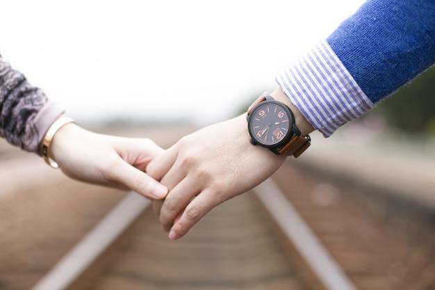 Close-up do casal segurando as mãos