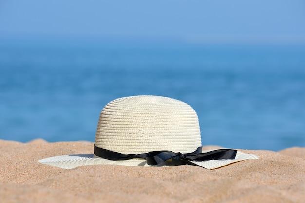 Close-up do chapéu de palha amarelo na praia de areia à beira-mar tropical em dia de sol quente. conceito de férias de verão.