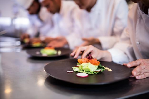 Close-up do chef decorando o prato de comida