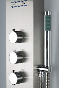 Close-up do chuveiro de aço inoxidável cromado moderno, para o banheiro moderno.