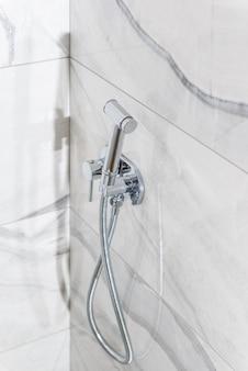 Close-up do chuveiro higiênico com ladrilhos cinza.
