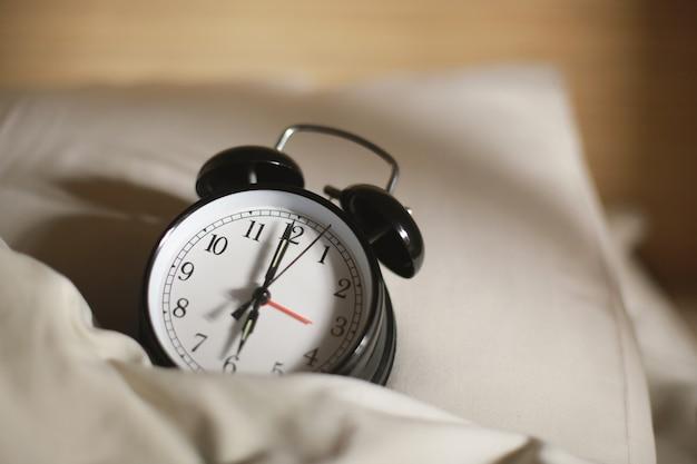 Close-up do clássico despertador preto na cama, marcando seis horas