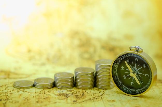 Close up do compasso no mapa do mundo com a pilha de moedas.
