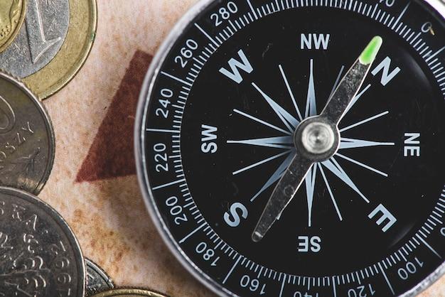 Close-up do compasso preto com algumas moedas
