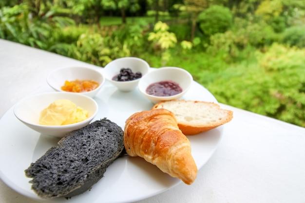 Close up do conjunto de pequeno-almoço delicioso, vários tipos de pão e geléia