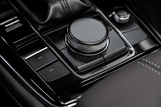 Close-up do console central moderno com botões no painel do carro, sem marcas registradas