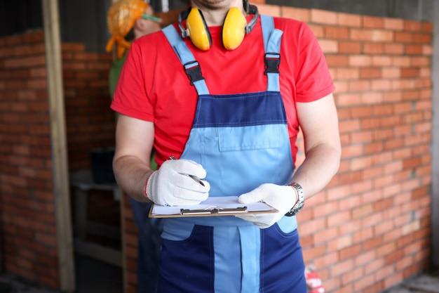 Close-up do construtor profissional na construção de uniforme.