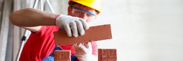 Close-up do construtor profissional que repara a casa. construtor profissional que coloca tijolos. homem de uniforme especial e capacete. conceito de reestruturação e construção