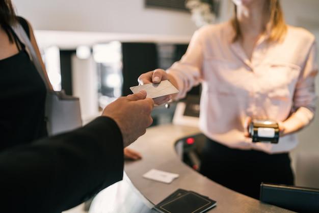 Close up do convidado faz o pagamento com cartão no check-in na recepção.