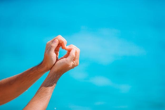 Close up do coração feito por mãos femininas no fundo do oceano turquesa