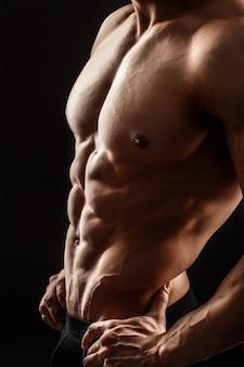 Close-up do corpo masculino perfeito, isolado na parede preta