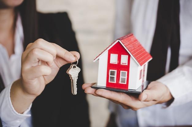 Close up do corretor de imóveis da mulher que dá a chave do apartamento novo ao cliente.