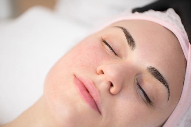 Close-up do cosmetologista faz o procedimento de injeções faciais de rejuvenescimento para apertar a pele do rosto de uma mulher em uma clínica de beleza.