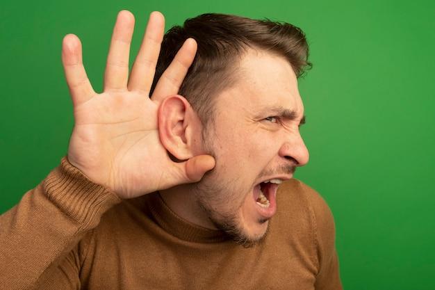 Close-up do curioso jovem loiro bonito mantendo a mão atrás da orelha olhando direto fazendo um gesto de não consigo ouvir você