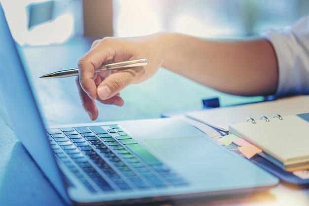 Close-up do dedo do empresário empurrando o botão enter no computador portátil
