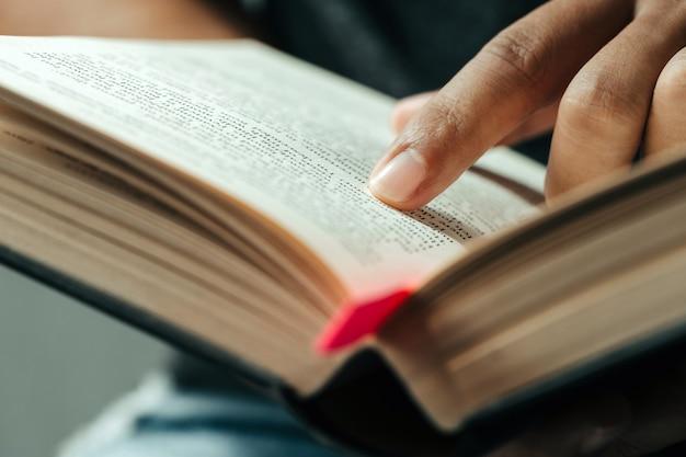 Close-up do dedo que aponta o texto em bible.close acima da leitura do homem através da bíblia.