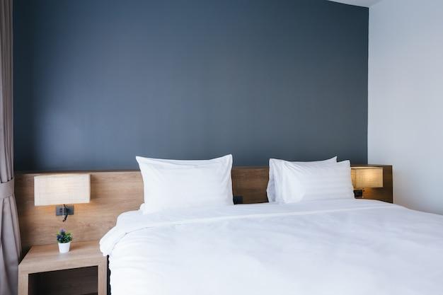 Close-up do descanso branco na decoração da cama com a lâmpada leve no interior do quarto do hotel.
