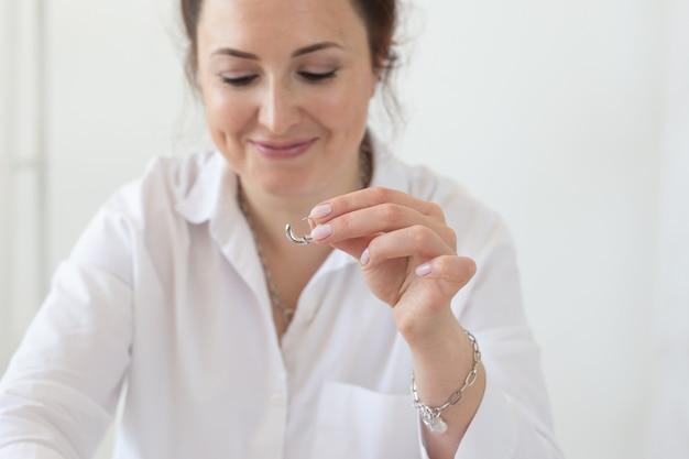 Close-up do designer de acessórios profissional, fazendo joias feitas à mão na oficina do estúdio. moda, criatividade e conceito artesanal.
