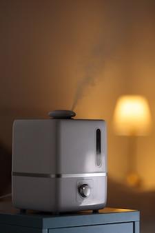 Close-up do difusor de óleo de aroma em cima da mesa em casa, vapor do umidificador de ar