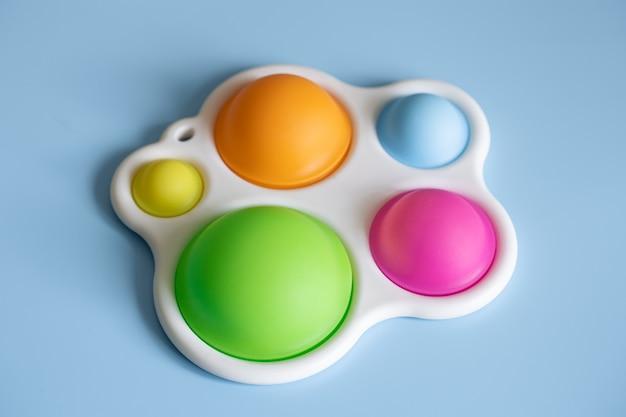 Close-up do display simples anti-stress de brinquedo da moda sobre um fundo azul.