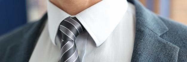 Close-up do empresário com gravata listrada e conceito de trabalho bem-sucedido de jaqueta