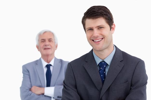 Close-up do empresário sorridente com seu chefe atrás dele