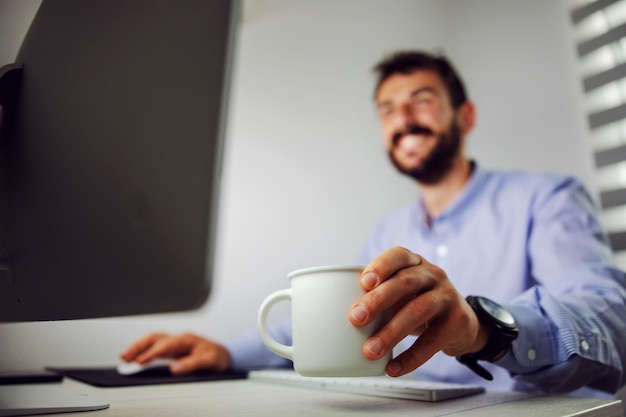 Close-up do empresário sorridente usando computador e segurando a caneca com café enquanto está sentado em seu escritório. foco seletivo na caneca.