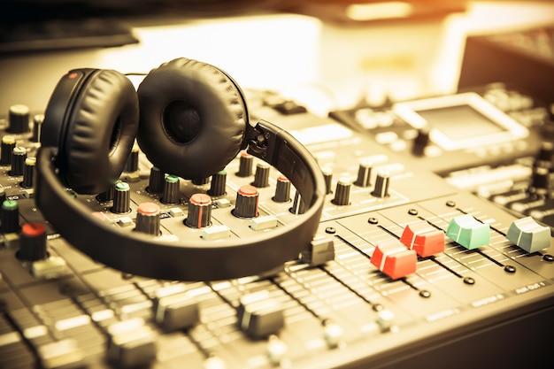 Close-up do fone de ouvido com mixer de áudio no local de trabalho do estúdio