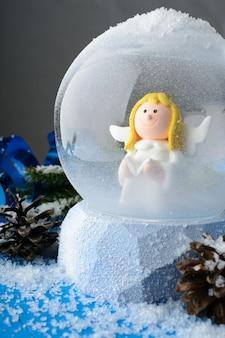 Close-up do globo de neve com anjo dentro em composição com decoração de natal na superfície azul nevada.