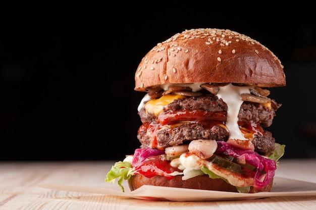 Close up do grande suculento hambúrguer duplo com molho branco, queijo, ketchup, pickles, cogumelos e cebola roxa em fundo preto com espaço de cópia. foco seletivo.