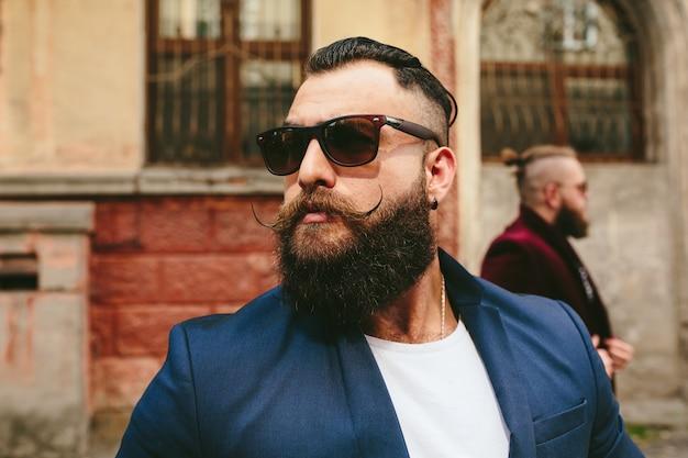 Close-up do homem à moda com barba e óculos de sol