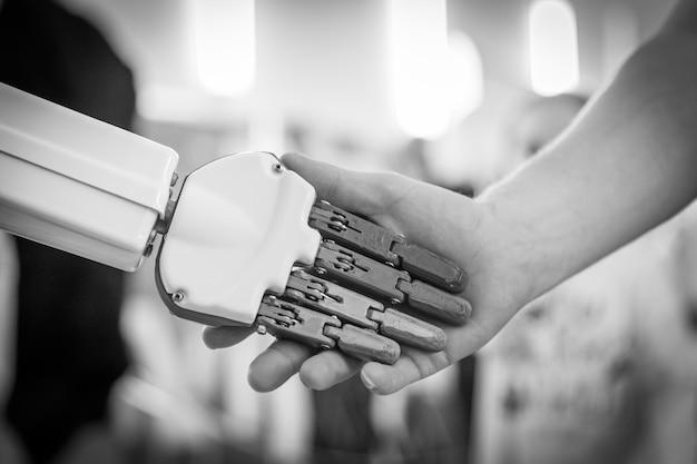 Close-up do homem apertando as mãos com um robô