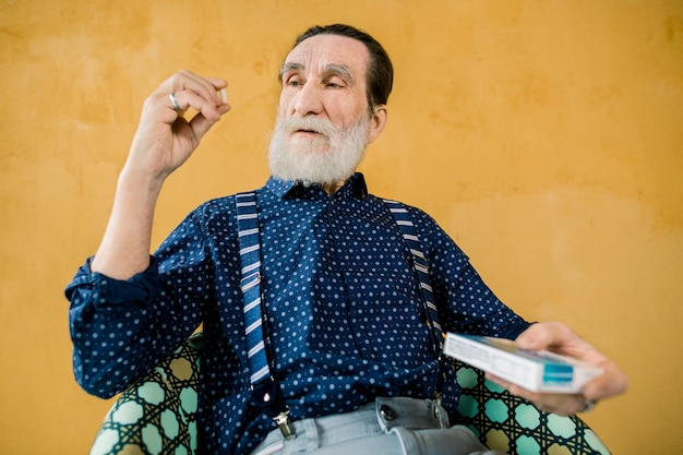 Close-up do homem barbudo sênior tomando pílula medicina, olhando para a cápsula branca na mão, sentado na cadeira em fundo amarelo