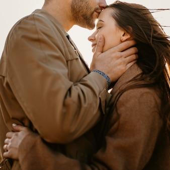 Close-up do homem beijando a mulher na testa