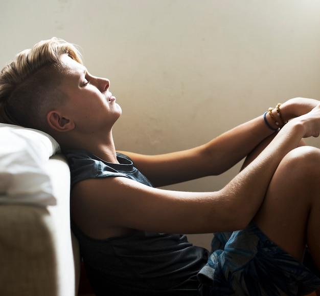 Close up do homem caucasiano novo que senta-se com a cara expressa da emoção virada deprimida