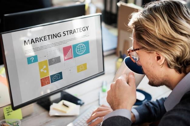 Close up do homem caucasiano que bebe o café com a tela de computador que mostra a estratégia de marketing